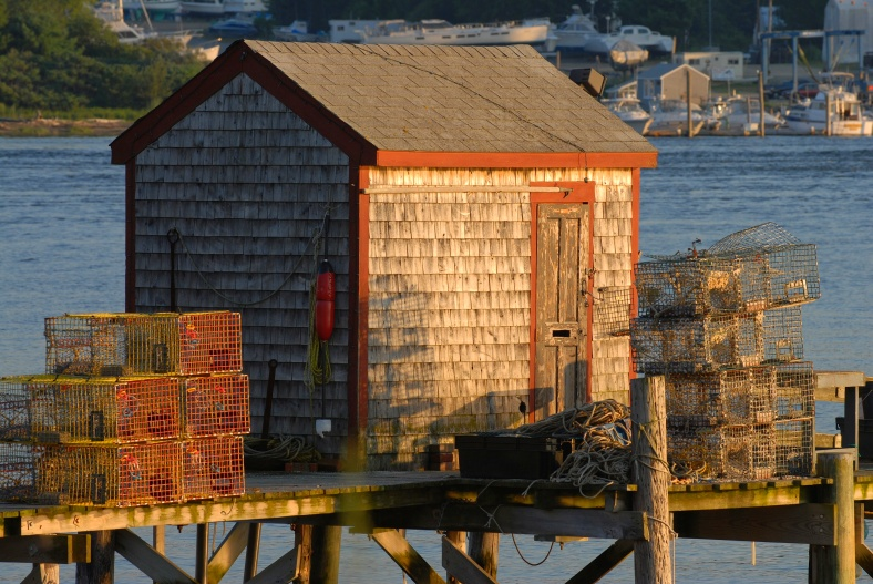 Golden light reflects off old fish shack and lobster traps as sun goes down in Little Bay on the Piscataqua River in Dover, NH.